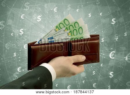 Businessman's hand takes out euro from a wallet with global exchange graphic