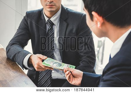 Businessman giving money Australian dollars to his partner - bribery and corruption concepts
