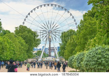 Paris France - May 2 2017: The Big Wheel at Place de la Concorde view from Tuileries Garden with the crowd and cloudy sky in evening on May 02 2017 in Paris France.