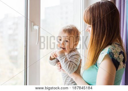 Loving mother playing with her baby son near a window.