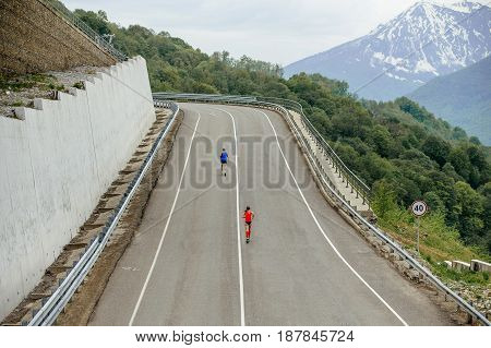 Rosa Khutor, Russia -  May 7, 2017: back two runners running mountain marathon serpentine asphalt road in race Spring mountain marathon