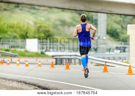 Rosa Khutor, Russia -  May 7, 2017: male runner in compression socks running in road with traffic cones safety in race Spring mountain marathon