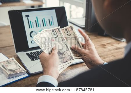 Businessman counting money Japanese yen banknotes at working desk
