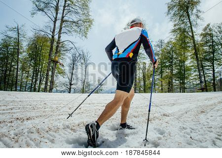 Rosa Khutor, Russia -  May 4, 2017: back male skyrunner running mountain snowy trail with trekking poles in race Vertical kilometer