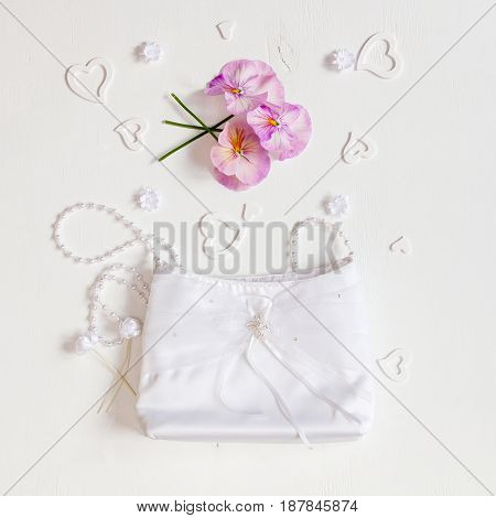 Wedding background. Handbag of the bride flowers and hearts on a white background.