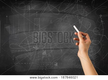 Female hand holding white chalk in front of a blackboard with scribbles and plans drawn on it