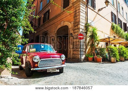 Rome Italy - May 3 2016. Red vintage car parked in the old street in Rome.