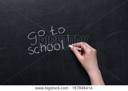 Human Hand Writing Phrase Go To School With Piece Of Chalk On Blackboard