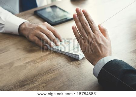 Businessman rejecting money that offered by a man- anti bribery and corruption concept