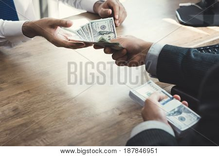Businessman giving money to partner at working desk - loan bribery and corruption concepts