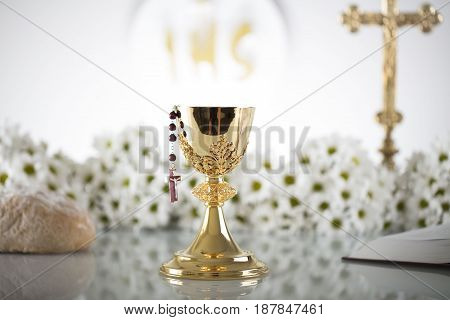 First Holy Communion. Catholic religion theme. Crucifix, Bible, bread isolated on white table and white background.