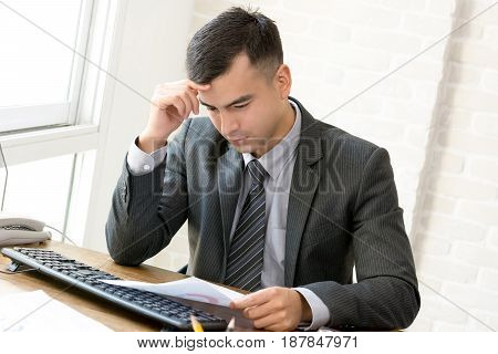 Businessman with hand on temple getting serious while reading document at working desk
