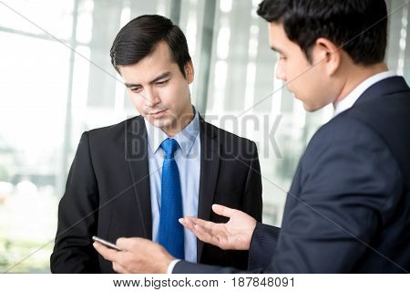 Two businessmen looking at smartphone and discussing at building hallway