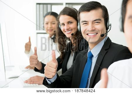 Smiling customer support team giving thumbs up in call center
