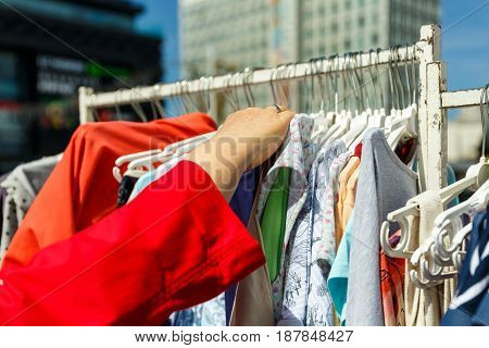 The hand chooses the clothes that hang on the hangers in the shop on the street