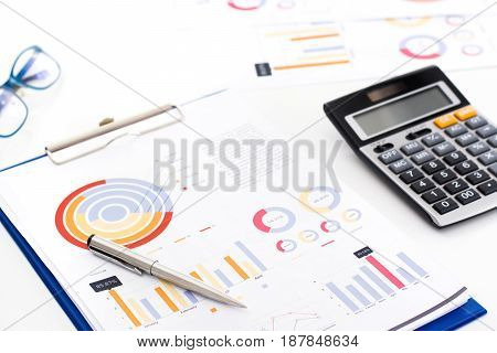 Financial graph data document on the table with calculator - selective focus