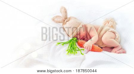 Very cute Two weeks old smiling newborn baby boy wearing knitted bunny costume, hat with rabbit ears, tail and funny carrot toy. Sweet new born baby portrait sleeping in his bed, isolated on white