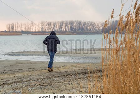 Back view of man walking on the river bank on cold autumn day