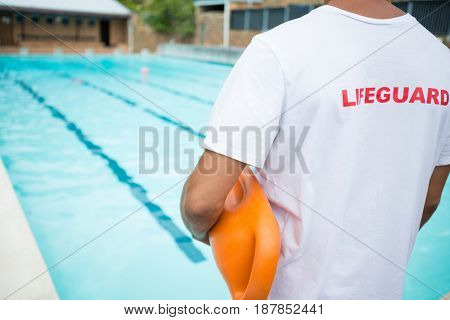 Rear view of lifeguard standing with rescue buoy near poolside