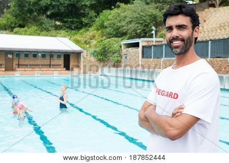 Portrait of smiling lifeguard standing with arms crossed in poolside