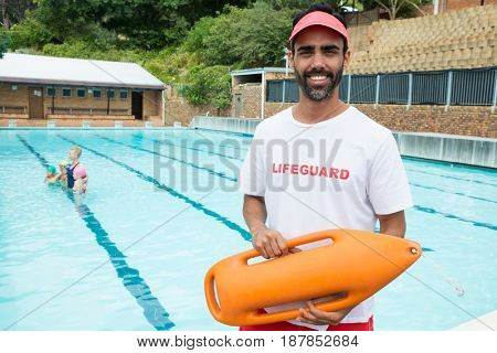 Portrait of lifeguard standing with rescue buoy near poolside