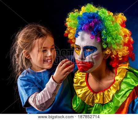 Single parent family. Tired mom after work as clown on birthday on dark background. Adult child relationship. Social problem mad parent.