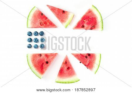 A culinary composition in the colors of the American flag, made up by blueberries and watermelon slices on a white background. Independence Day greeting card, 4th of July banner, with copy space