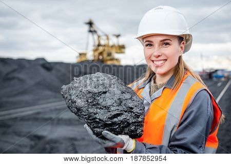 worker with piece of coal in her hand at an open pit