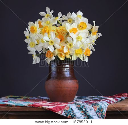 Still life in rustic style. A bouquet of fresh garden daffodils in a clay jug on the table.