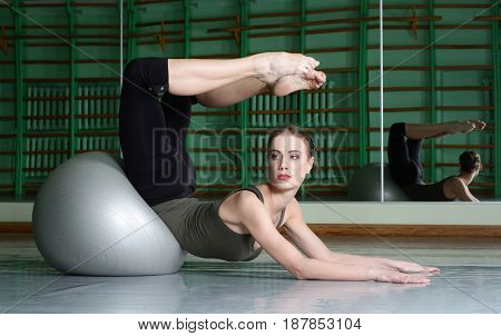 Attractive Woman Exercising With Exercise Ball At dance hall