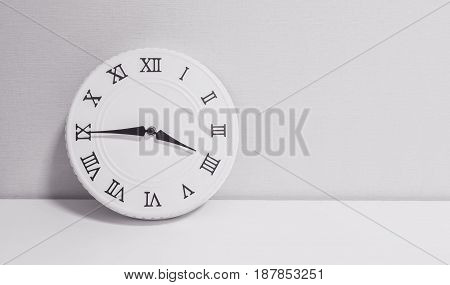 Closeup white clock for decorate show a quarter to four o'clock or 3:45 p.m. on white wood desk and wallpaper textured background in black and white tone with copy space