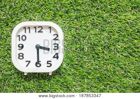 Closeup white clock for decorate show a half past three o'clock or 3:30 p.m. on green artificial grass floor textured background with copy space