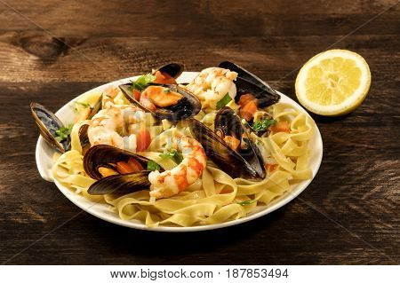 A photo of a ready to eat seafood pasta dish with mussels and shrimps, on a dark wooden rustic background texture, with a lemon half and a place for text