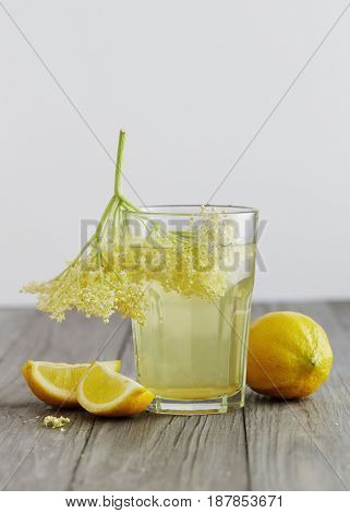 Elderflower juice with lemons and elderflowers on a wooden table