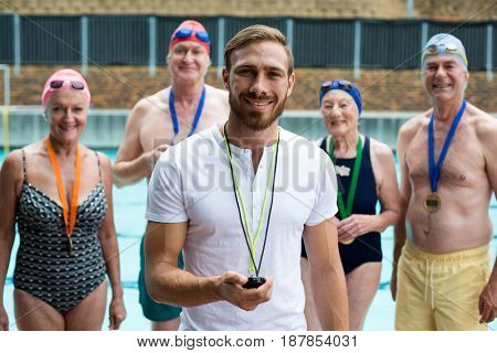 Portrait of instructor with senior men and women at poolside