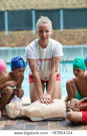 Portrait of female lifeguard demonstrating children during rescue training