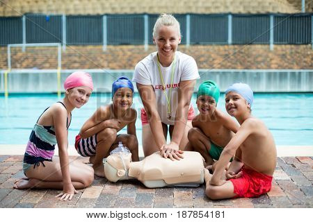 Portrait of cheerful female lifeguard and children during rescue training
