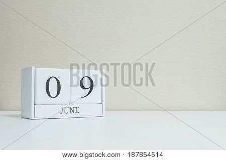 Closeup white wooden calendar with black 9 june word on blurred white wood desk and cream color wallpaper in room textured background with copy space selective focus at the calendar