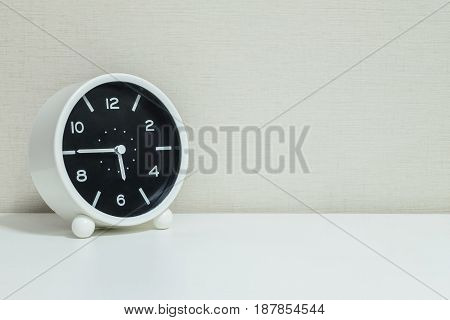 Closeup black and white alarm clock for decorate in a quarter to six o'clock or 5:45 p.m. on white wood desk and cream wallpaper textured background with copy space