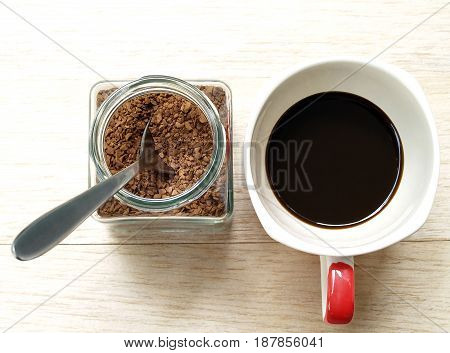 instant coffee with silver spoon in small transparent glass jar and black coffee in ceramic coffee cup on wooden floor, close-up top view