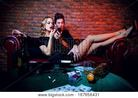 Glamorous couple of young people spending time at night club or casino. Entertainment industry. Beauty, fashion concept.