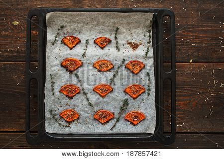 Tray with baked slices of pumpkin flat lay. Top view on kitchen table with roasted squash with spices, free space. Seasonal cuisine, healthy food, menu concept