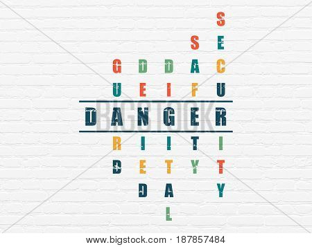 Security concept: Painted blue word Danger in solving Crossword Puzzle
