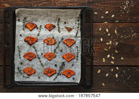 Baked pumpkin tray on table with seeds flat lay. Top view on wooden kitchen background with prepared spiced squash slices. Seasonal menu, healthy food, vegetarian menu concept