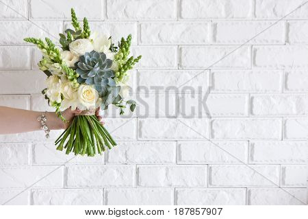 Female hand gives bunch with roses and succulent on white brick background. Gift for mother or woman, florist work, wedding decor, beautiful bouquet sale concept