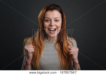 Exciting news. Bright gorgeous young girl looking emotional while supporting her friend and standing isolated on grey background