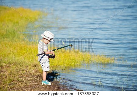 Little Boy Fishing On A Lake. Color Image. Toned Image