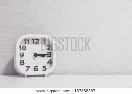 Closeup white clock for decorate show a quarter past three o'clock or 3:15 p.m. on white wood desk and cream wallpaper textured background in black and white tone with copy space