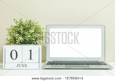 White wooden calendar with black 1 june word with white blank space at center of computer notebook on white wood desk and cream wallpaper textured background selective focus at the calendar