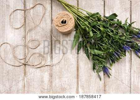 Workplace with wildflower and rope flat lay. Floristry workshop wooden table with decor. Decorative artwork from spring flower